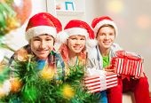 Cute teen children with presents by Christmas tree