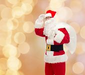 christmas, holidays and people concept - man in costume of santa claus with bag looking far away over beige lights background