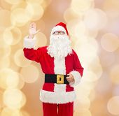 christmas, holidays, gesture and people concept - man in costume of santa claus waving hand over beige lights background