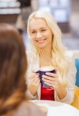 drinks, communication, friendship and people concept - happy young women with coffee cup sitting at table and talking in mall or cafe