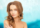 beauty, people and health concept - beautiful young woman with bare shoulders over blue ripple water background