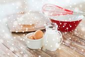 cooking, home and food concept - close up of milk jug, eggs in a bowl, whisk and flour