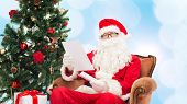 christmas, holidays and people concept - man in costume of santa claus with letter over blue lights background