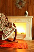Rocking chair with plaid near fireplace