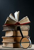 Pile Of Old Books With Magnifying Glass