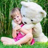 Little Cute Girl Sitting In The Grass With Large Teddy Bear