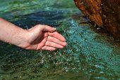 Beautiful woman hand in clear mountain water