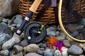 pic of fly rod  - Close up of fishing fly reel landing net creel and assorted flies on dry river bed rocks - JPG