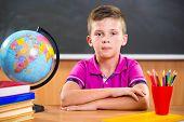 picture of diligent  - Cute diligent boy sitting in classroom in front of blackboard - JPG