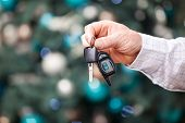 Male hand holding car key on Christmas background