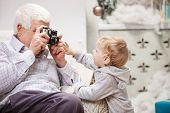Senior man taking photo of his toddler grandson