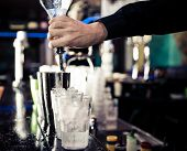 image of bartender  - bartender pouring alchol into the tin - JPG