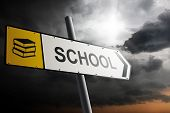 School Direction. Yellow Traffic Sign With Cloudy Sky In The Background.