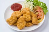 Chicken Nuggets On A Plate With Sauce And Vegetables On The Plate On White Background.