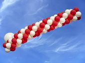Red And White Balloons Isolated On Blue Sky Background