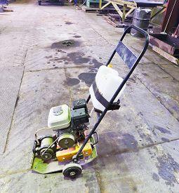 stock photo of vibration plate  - small gasoline vibratory plate on concrete road - JPG