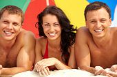 picture of young adult  - Portrait of happy girl between two guys lying on sand on summer vacation - JPG