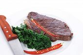 stock photo of kale  - grilled beef steak meat with red hot pepper and fresh raw kale leaf served on white plate isolated over white background - JPG