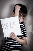 image of abused  - Scared and abused young boy holding the paper with handwritten help sign - JPG