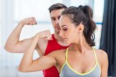 picture of muscle builder  - Active athletic sportive woman girl and man showing their muscles biceps healthy lifestyle.