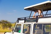 pic of  jeep  - Young blond lady on safari standing in open roof jeep observing wild animals through binoculars - JPG