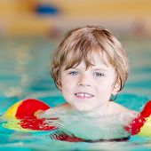 picture of floaties  - Adorable little kid boy with swimmies learning to swim in an indoor pool - JPG
