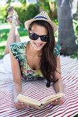 stock photo of palm-reading  - Smiling beautiful brunette lying and reading a book with palm tree behind her - JPG