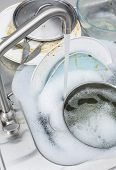 foto of dirty  - Washing dirty dishes in a kitchen sink - JPG