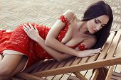 image of lace  - fashion outdoor photo of beautiful sensual woman with dark hair in luxurious lace red dress - JPG