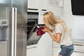picture of oven  - very pretty young blond woman in act of looking some food with oven in her luxury white modern kitchen - JPG
