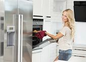 stock photo of oven  - commercial shot of young girl smiling and cooking with oven in her luxury kitchen - JPG