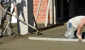 stock photo of concrete pouring  - Picture of a workers smooth concreting the floor - JPG