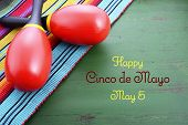 stock photo of mexican fiesta  - Happy Cinco de Mayo background with colorful maracas on Mexican theme dark green distressed table with copy space - JPG
