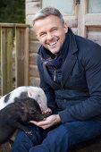 pic of pig  - Mature Man Feeding Pet Micro Pig - JPG