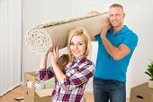 pic of carpet  - Happy Young Couple Carrying Rolled Carpet In Their New Home - JPG
