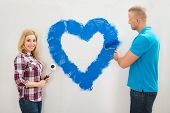 picture of wall painting  - Portrait Of Young Couple Painting Heart On Wall With Blue Paint - JPG