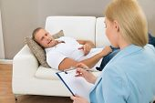 stock photo of psychologist  - Female Psychologist Making Notes During Psychological Therapy Session - JPG