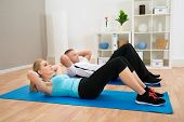 picture of crunch  - Portrait Of Young Couple Doing Crunches On Exercising Mat - JPG