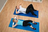 stock photo of crunch  - High Angle View Of Young Couple Doing Crunches On Exercising Mat - JPG
