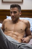 image of shirtless  - Shirtless sexy male model lying alone on his bed in his bedroom - JPG