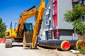pic of backhoe  - Excavator loader with backhoe is standing over blue sky in city street - JPG