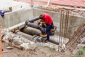 image of pipe-welding  - Metal worker is grinding weld on pipe junction completing a manhole for heating pipeline system - JPG