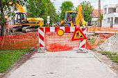 foto of road construction  - Road is closed for construction site witch is protected by several traffic signs and orange fence with flashing beacon lights - JPG