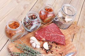image of peppercorns  - raw beef meat fillet with peppercorn and thyme and different spices in glass bottles ready to grill on wood figured aged board over table - JPG