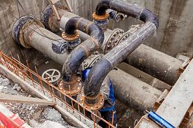 image of pipe-welding  - Welder is welding pipe junction completing a manhole for heating pipeline system - JPG