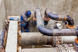 image of pipeline  - Welder is welding pipe junction completing a manhole for heating pipeline system - JPG