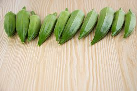 picture of okra  - Fresh okra on the wooden table background - JPG