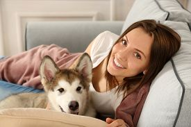pic of laika  - Young woman lying with malamute dog on sofa in room - JPG