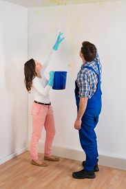 stock photo of leak  - Young Woman With Bucket Showing Water Leaking From Damage Ceiling To Maintenance Guy - JPG