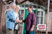 Happy Senior Wife Holding Keys Of New House While Her Husband Shaking Hands With Saleman poster